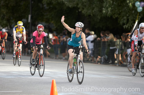 A Biker waves to a friend in the crowd who has come out to cheer everyone on.