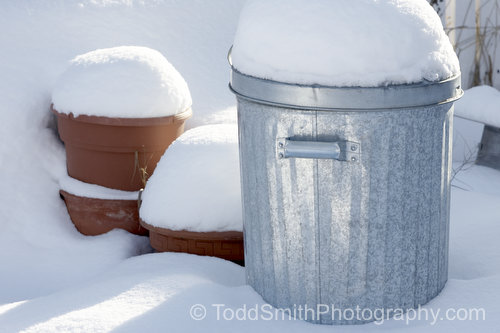 flowerpots and trash can in snow